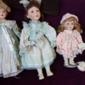 Value of Leonardo Collection Porcelain Dolls - three dolls on a black background