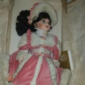 Value of a Franklin Heirloom Doll - doll wearing a bright pink outfit with white fur trim and matching hat