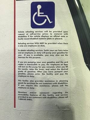 A gas station sign with information for handicapped customers.