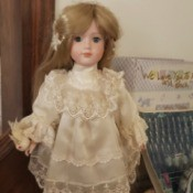 Identifying a Porcelain Doll - doll wearing a lace trimmed off-white dress