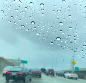 A windshield that is clear at the bottom and with water spots at the top.