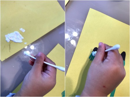 Making a Dandelion Card - Toddler Activity - child applying the paint with a Q-tip