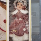 Value of a Seymour Mann Porcelain Doll - doll in box wearing a dusty rose outfit with white fur trim