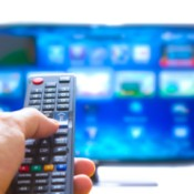 A television remote pointed at a smart TV with lots of apps.