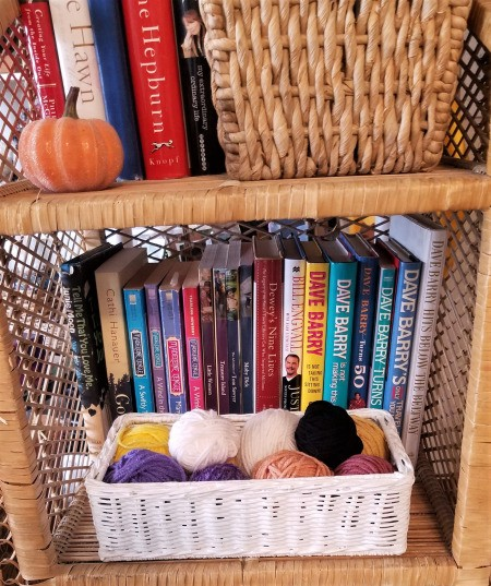 A wicker tissue box used to store yarn.