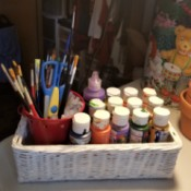 A wicker tissue box used to store paints.