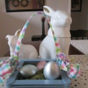 Craft Stick Basket  - blue basket with spring colored checkered ribbon handle and pearlized eggs inside, sitting in front of two white ceramic rabbits