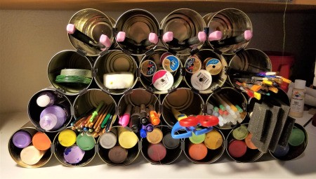 Tin Can Craft Supply Organizer - filled with supplies, can lids placed under bottom row to tilt it back a bit, see final photo