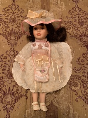 Value of an Unidentified Porcelain Doll - doll wearing a pretty pink dress with a matching hat