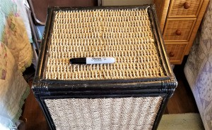 A scratched wicker hamper with a black Sharpie on top.
