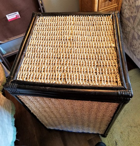 A wicker hamper with scratches colored in with a black Sharpie.