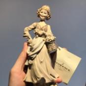 Value of a Giuseppe Armani Figurine - hand holding a tan figurine