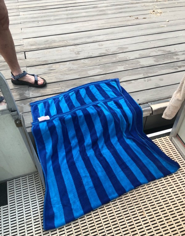 Placing a towel as a bridge between the boat and the dock.