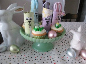 Recycled Bunny Friends - cake plate with bunnies among the cupcakes surrounded by two white ceramic bunnies and plastic eggs