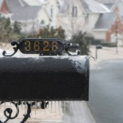 A house number on a mailbox in the snow.