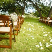 An outdoor wedding with white petals down the center.