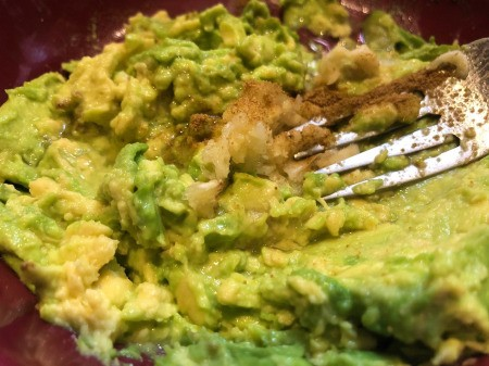 adding spices to Avocado & mixing with fork