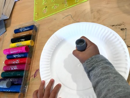 Spring Paper Plate Flower Craft - child beginning to create decorated plate