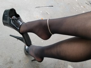 Sexy legs in black sheer pantyhose and high heeled shoes.
