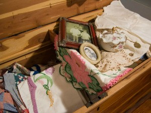 A hope chest with old fashioned linens and photos.