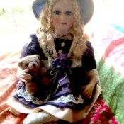 Value of Porcelain Dolls - doll wearing a hat and holding a teddy bear