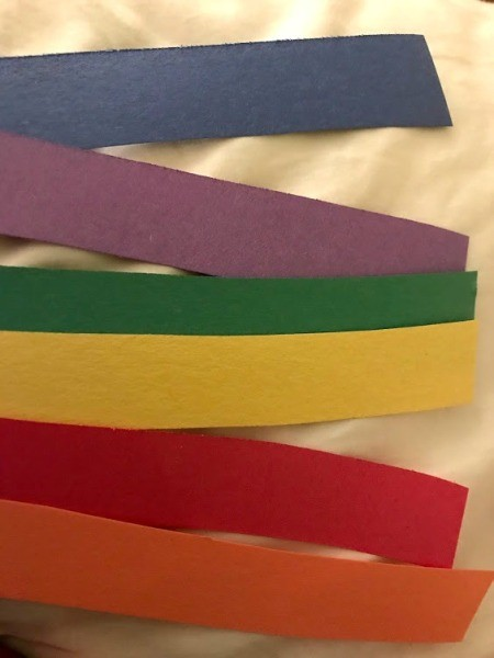 Making a Paper Plate Rainbow - cut out rainbow colored strips of paper