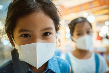 Two girls with masks on to prevent respiratory infections.