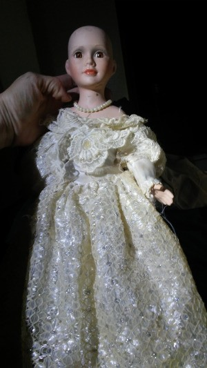 Identifying a Porcelain Doll - hairless doll wearing a pretty lacy dress and pearls