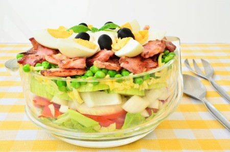 A green layered salad in a clear bowl.