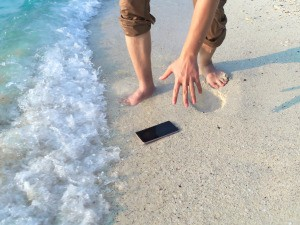 A phone dropped in the surf at the beach.