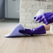 A pair of gloved hands cleaning a table with a spray bottle and a rag.