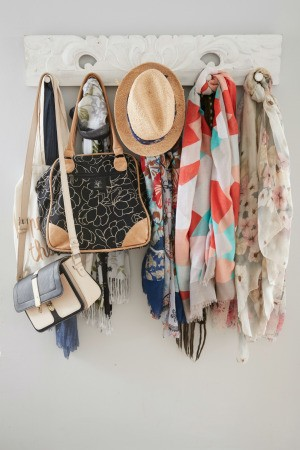 A hanging coat rack with hat, scarves and purses stored on it.