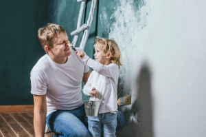 A little girl helping her father primer a wall.