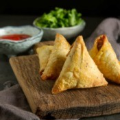 Indian samosas with sauce and herbs.