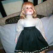 Value of an Ashley Belle Doll - doll wearing a white top with a dark flower trimmed skirt over a tan underskirt