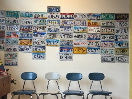 A collection of license plates on a wall at the DMV.