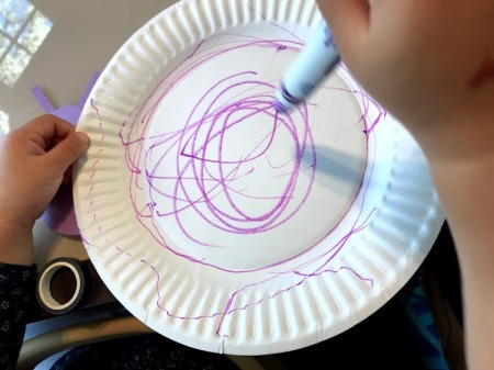 Snail Paper Plate Craft - child decorating shell (paper plate) with a marker