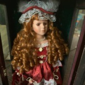 Value of an Ashley Belle Doll - doll with long ringlets wearing a maroon dress