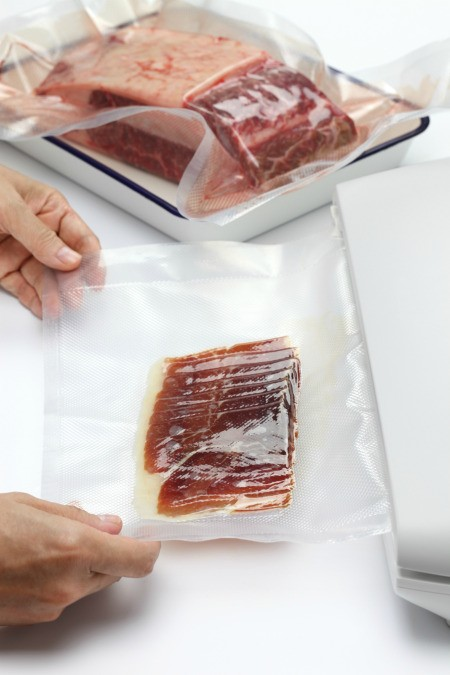 Vacuumed sealed bags of meats in a kitchen.