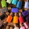 Colorful beads in small glass jars.