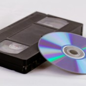 A VHS tape next to a DVD disk.