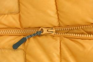 Close up of a yellow jacket zipper.