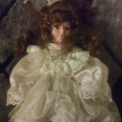Identifying a Porcelain Doll - doll wearing a satin and lace white dress