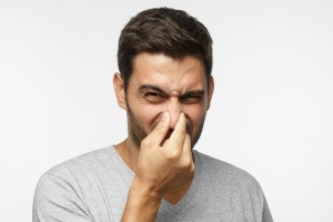 A man holding his nose from a bad smell.