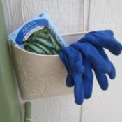 Bucket Garden Storage - newly painted pail on side of garden shed with seed packet and garden gloves inside