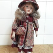 Identifying a Porcelain Doll - doll wearing a floral and plaid dress with matching hat