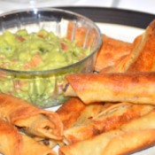 A plate of fried beef taquitos served with guacamole.