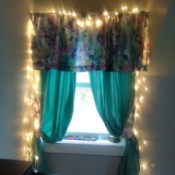 """A window treatment with white Christmas """"fairy"""" lights framing it."""