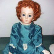 Identifying a Porcelain Doll - red haired doll wearing a old style blue dress