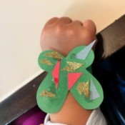 Making a Kid's Paper Butterfly Bracelet - child wearing the green butterfly